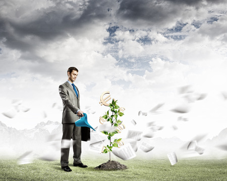Image of businessman watering money tree with currency symbols photo