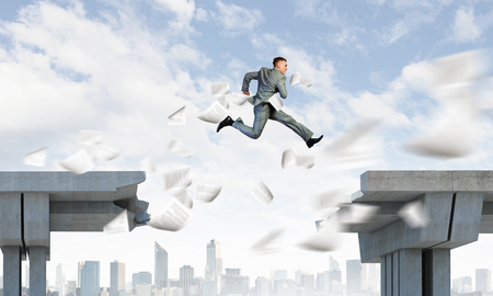Image of young businessman jumping over gap in bridge Stock Photo - 23500299