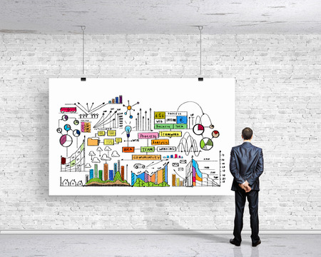 Image of businessman standing with back and looking at banner with business plan photo