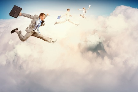 Image of happy business people jumping high in sky photo