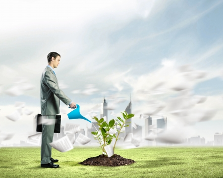 Image of businessman watering sprout with can photo