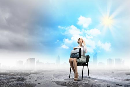 スーツケースを持って椅子に座っている若い実業家のイメージ