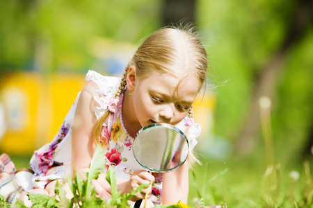Image of cute boy playing in park with magnifier photo