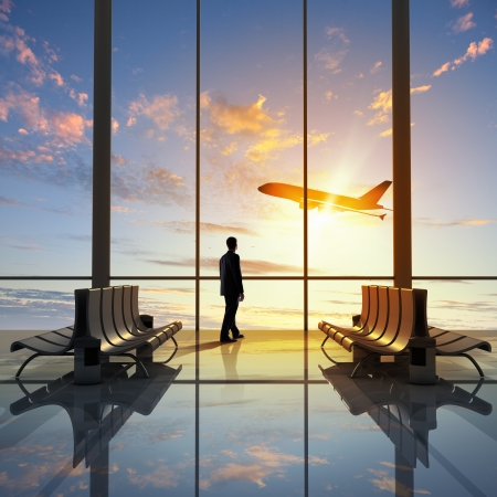 airport people: Businessman at airport looking at airplane taking off Stock Photo