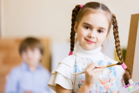 Little cute girl with paint brush and easel photo