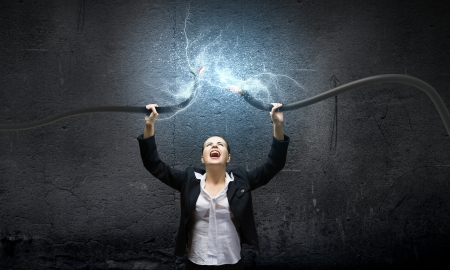 Image of businesswoman holding electrical cable above head photo