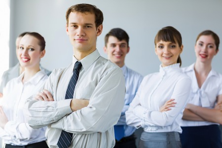 Young business people standing with arms crossed on chest photo