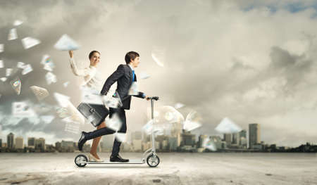 Image of young happy businesspeople riding scooter photo