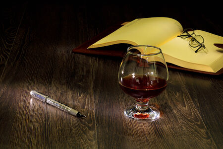 A glass with cognac, cigar and an old book nearby photo