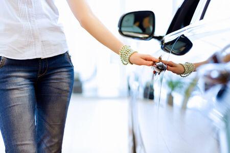 Pretty woman standing near car at car center  Choosing a car Stock Photo - 23696164