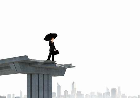 Image of businessman with umbrella standing at the edge of bridge photo