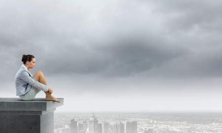 Image of young attractive businesswoman sitting alone atop of building photo