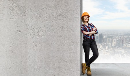 Image of young woman builder wearing helmet and leaning on blank wall photo
