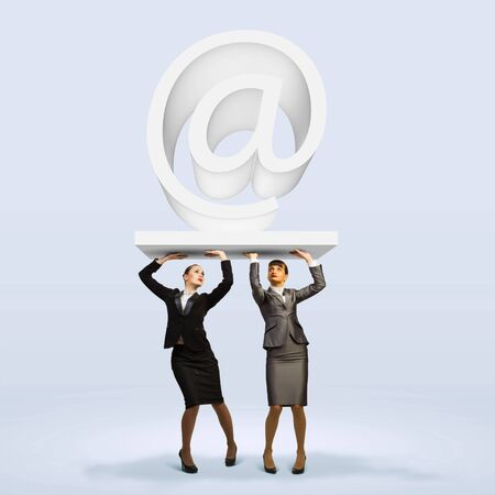 cohesion: Image of two businesswomen holding at symbol  Partner and cohesion Stock Photo