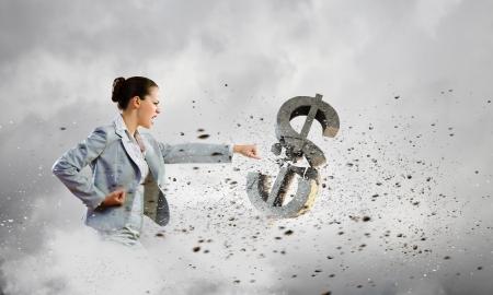 Image of businesswoman breaking stone dollar symbol