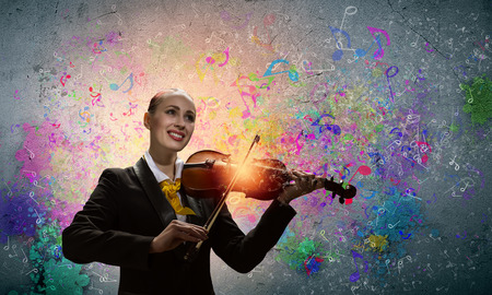 solo violinist: Image of young smiling businesswoman playing violin