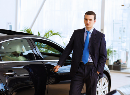 Image of handsome young businessman in suit standing near car photo