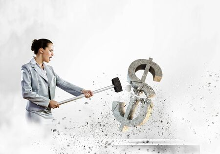 Image of businesswoman breaking stone dollar symbol with hammer photo
