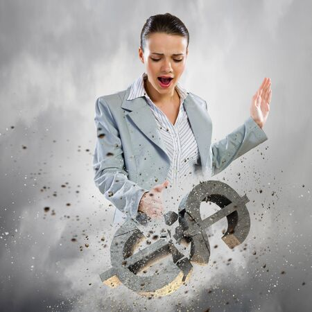 Image of businesswoman breaking stone dollar symbol photo
