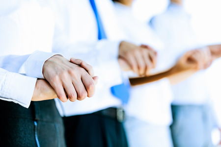 trust: Image of group of businesspeople holding arms together  Teamwork