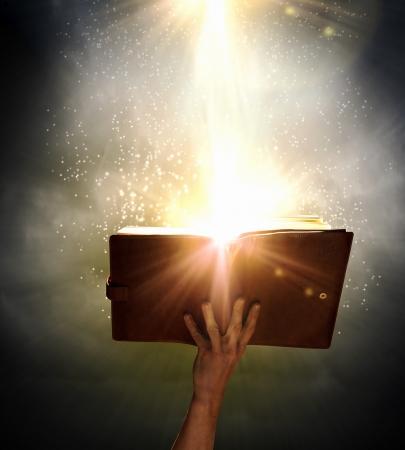 La mano del hombre que sostiene el libro mágico con luz mágica Foto de archivo - 23844018