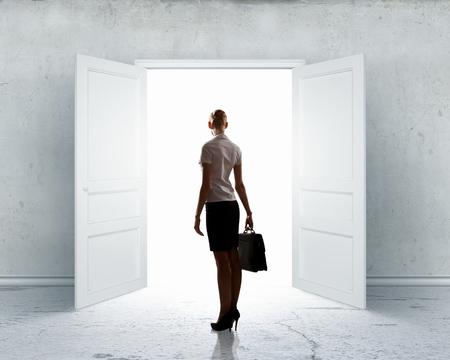 Image of businesswoman standing in front of opened door