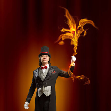 Image of man magician showing trick against color background Stock Photo - 23876691