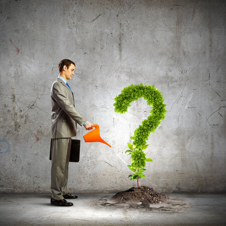 Image of businessman watering green question mark photo