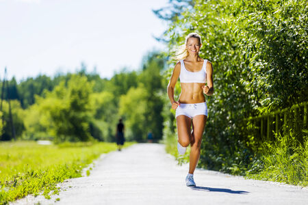 run out: Image of young attractive woman running outdoor