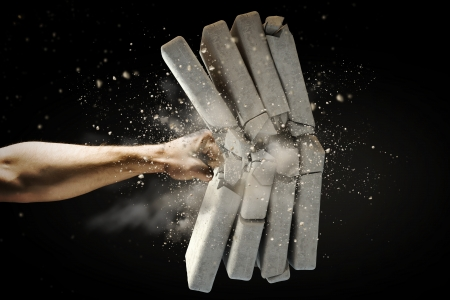 Close up of human hand breaking bricks Stock Photo