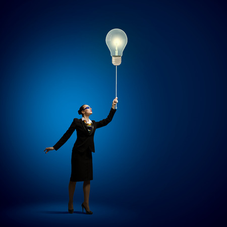 Image of businesswoman holding bulb balloon  idea concept photo