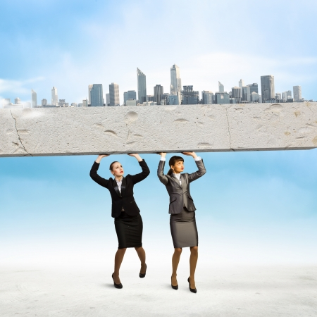 Image of two businesswomen holding stone above head  Partnership and cohesion photo