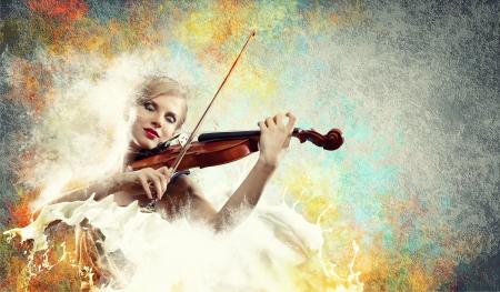 Image of beautiful female violinist playing with closed eyes against splashes background photo
