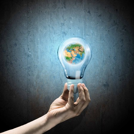 Image of human hand holding bulb with earth planet inside  Elements of this image are furnished by NASA photo