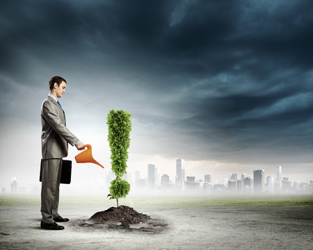 Image of businessman watering plant shaped like exclamation mark Stock Photo