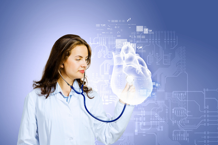 Image of young woman cardiologist with stethoscope examining heart