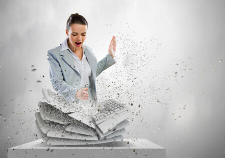 Image of businesswoman crushing with hand pile of keyboards photo
