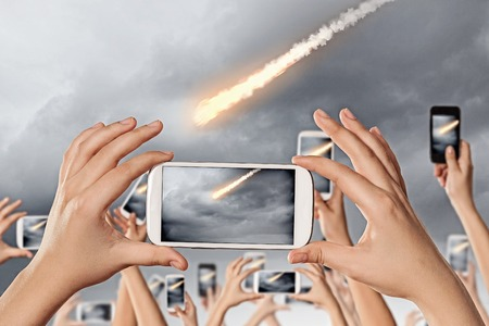 People taking photos of falling meteorite on mobile phone camera photo