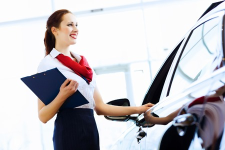 Young attractive woman consultant of car center standing near car photo