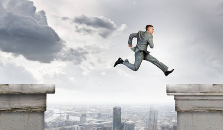 Young businessman jumping over bridge gap  Risking in business photo
