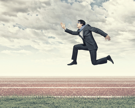Funny image of running businessman at stadium  Competition concept photo