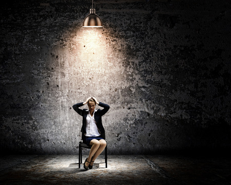 new job: Image of young businesswoman sitting on chair under spot of light Stock Photo