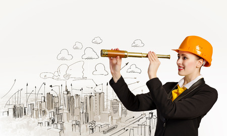 Image of young woman looking into tube  Construction concept photo