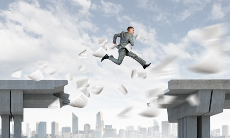 risking: Young businessman jumping over bridge gap  Risking in business Stock Photo
