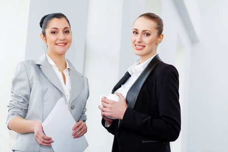 Image of two young pretty businesswomen smiling photo