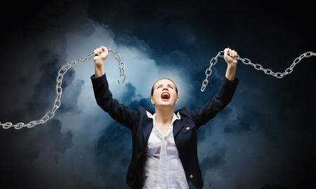 Afbeelding van zakenvrouw in woede breken metalen ketting