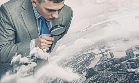 Image d'homme d'affaires l'examen d'objets avec la loupe