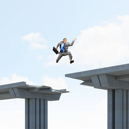 Businessman jumping over a gap in the bridge as a symbol of bridge photo