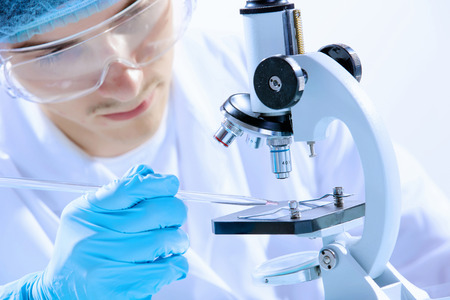 Image of man scientist working in laboratory with microscope photo