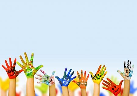 � image: Imagen de manos humanas en la pintura de colores con sonrisas Foto de archivo
